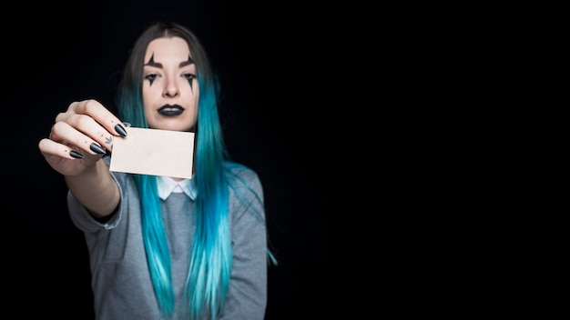 Young blue haired woman holding little paper card