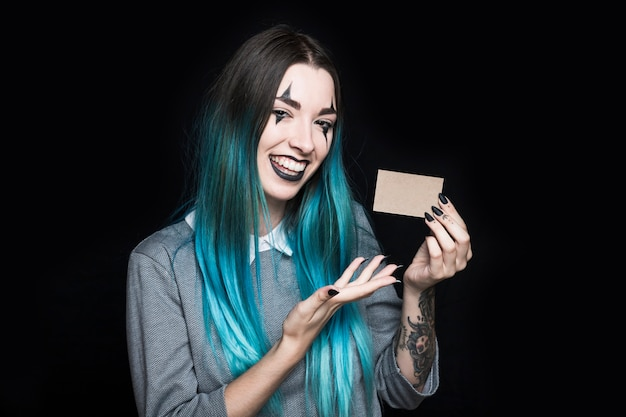 Young blue haired woman holding paper card