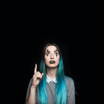 Young blue haired woman pointing with finger up