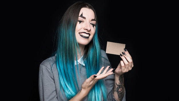 Young blue haired woman showing little card