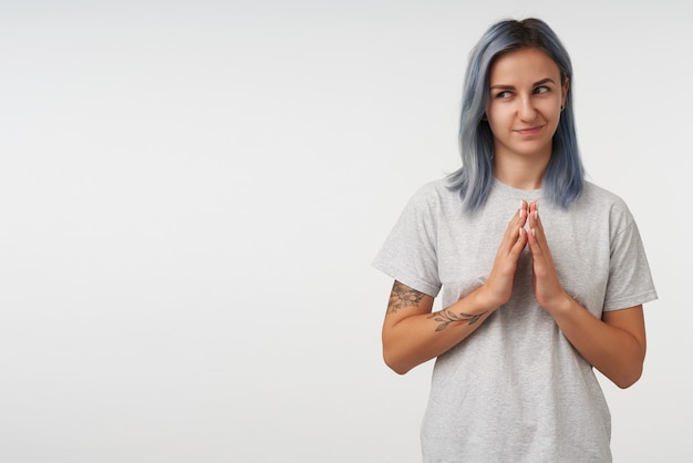 Young blue haired woman tattoos folding raised hands and looking cunningly aside, dressed in grey basic t-shirt while posing on white