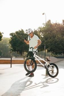 Young bmx rider looking at his phone long shot