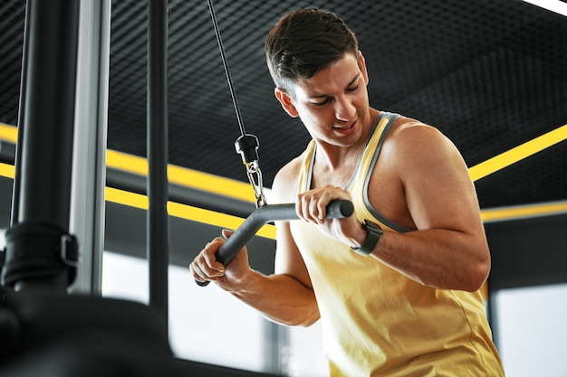 Young bodybuilder doing heavy weight exercise for biceps in a gym