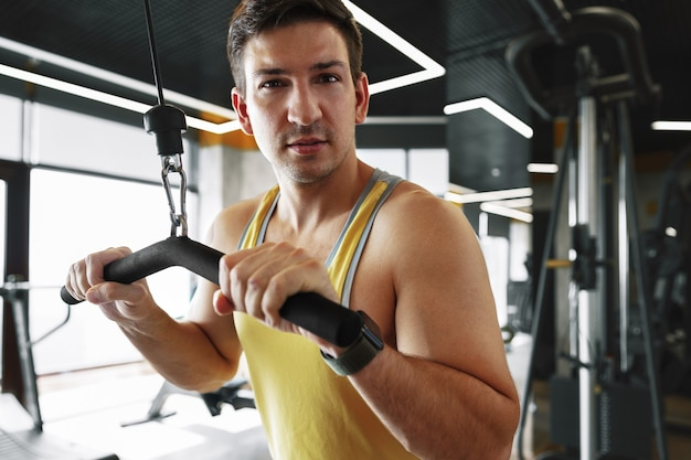 ジムで上腕二頭筋の重い重量運動をしている若いボディービルダー