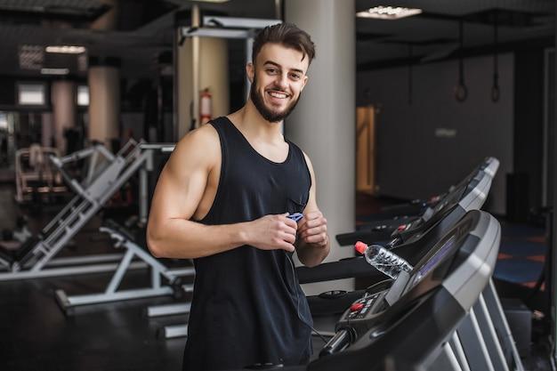 Молодой культурист делает кардио-тренировку и позирует в тренажерном зале