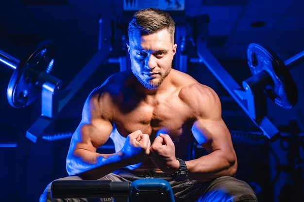 강한 몸이 체육관에서 운동 후 쉬고있는 젊은 보디