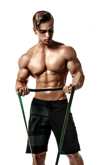 Young bodybuilder working out with rubber band over white background
