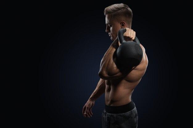 Молодой бодибилдер держит гирю сильный фитнес-мужчина делает кроссфит с гирей в тренажерном зале
