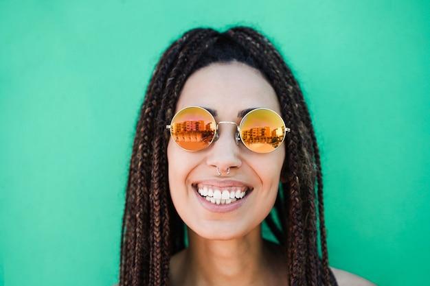 夏休みに屋外でカメラを見ている若いボヘミアン女性-顔に焦点を当てる Premium写真