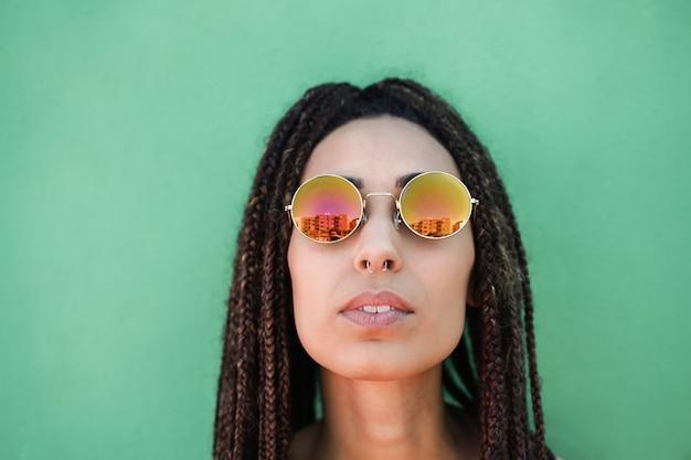 녹색 배경으로 야외에서 카메라를 바라보는 젊은 보헤미안 여성 - 얼굴에 초점