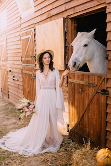 Young boho style bride is stroking white horse
