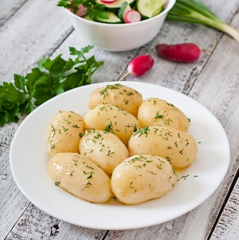 バターとディルの白い皿に若いゆでポテト