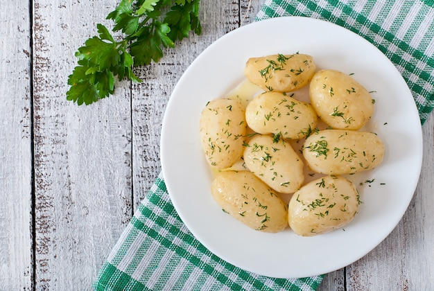 Young boiled potatoes with butter and dill on a white plate