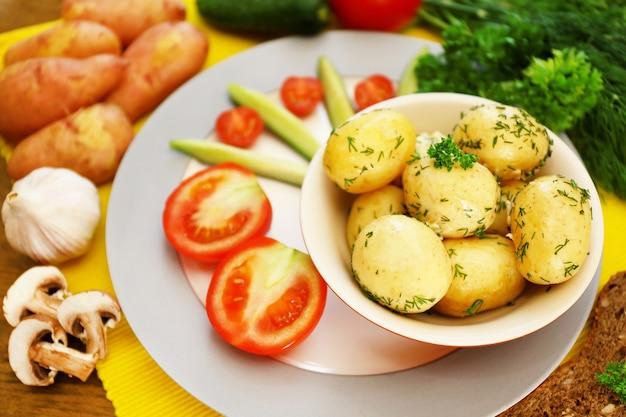 Молодой вареный картофель с овощами на столе