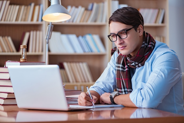 Young book writer writing in library