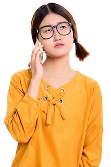 Молодая скучающая азиатская женщина разговаривает по мобильному телефону