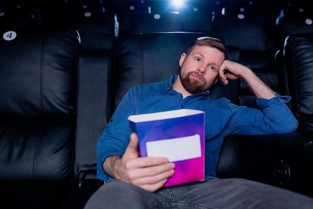 Молодой скучающий человек с коробкой попкорна сидит на черном кожаном кресле перед большим экраном в кинотеатре