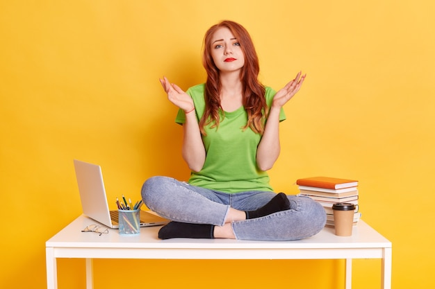 Молодая скучающая женщина носит зеленую футболку и джинсы