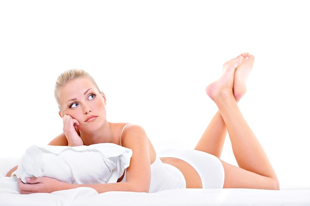 Young bored woman with lying down ot he bed over white