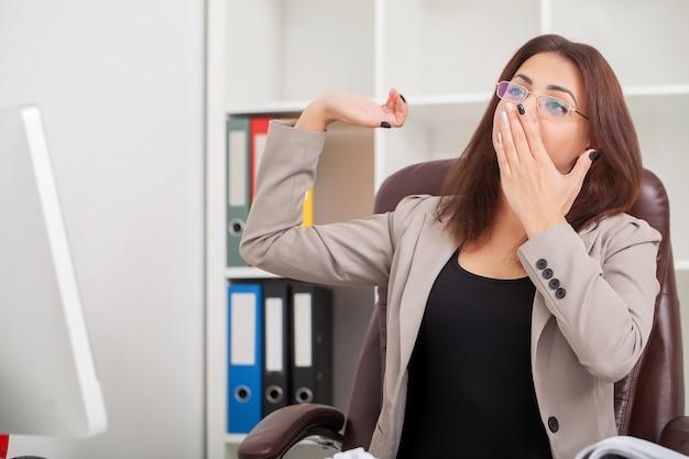 Молодая скучная деловая женщина сидит за столом с ноутбуком и хочет спать, пока зевает на рабочем месте в современном офисе