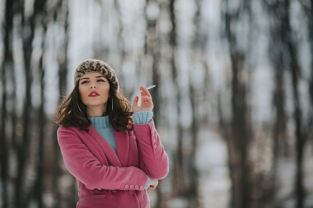 겨울에 숲에서 담배를 피우고 포즈를 취하는 젊은 보스니아 여성
