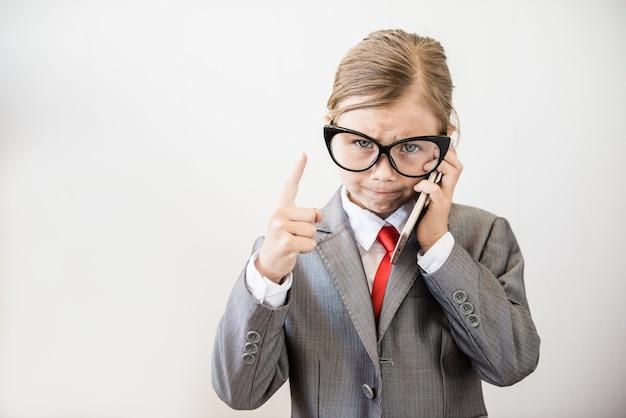 若い上司の女の子が電話で話します。怒っている実業家
