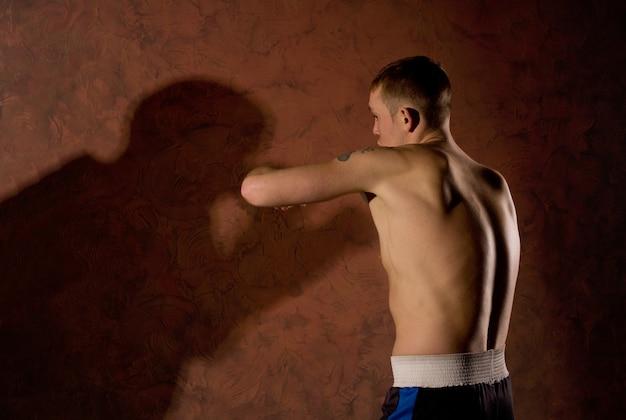 그림자 상대와 싸우는 젊은 권투 선수