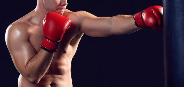 검정 배경 위에 빨간 장갑 권투에 젊은 권투 선수
