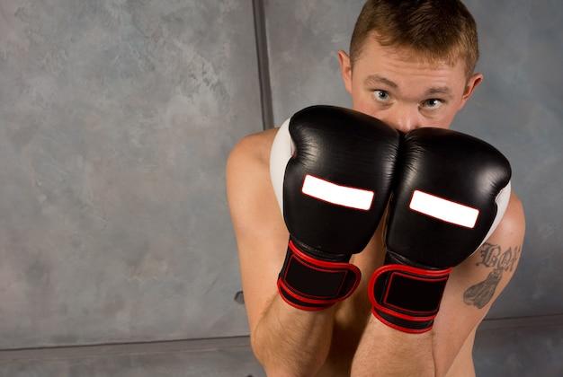 顔と頭を守る若いボクサー