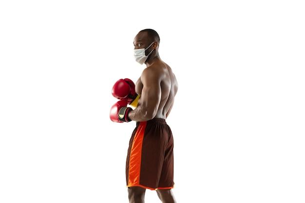 Giovane pugile in maschera protettiva e guantoni da boxe