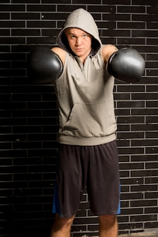 Young boxer punching with both of his gloved fists towards the camera