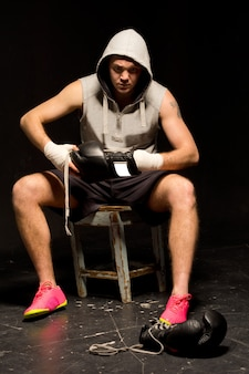 Young boxer sitting on a stool at the side of a ring during training putting on his gloves