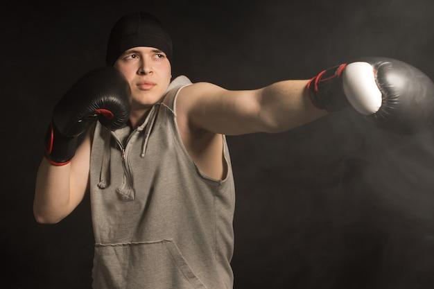 그의 장갑 낀 주먹으로 펀치를 던지는 젊은 권투 선수