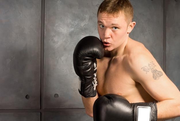 ワークアウトの入れ墨を持つ若いボクサー