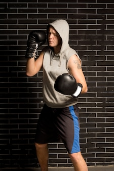 Young boxer working out during training standing in front of a dark brick wall