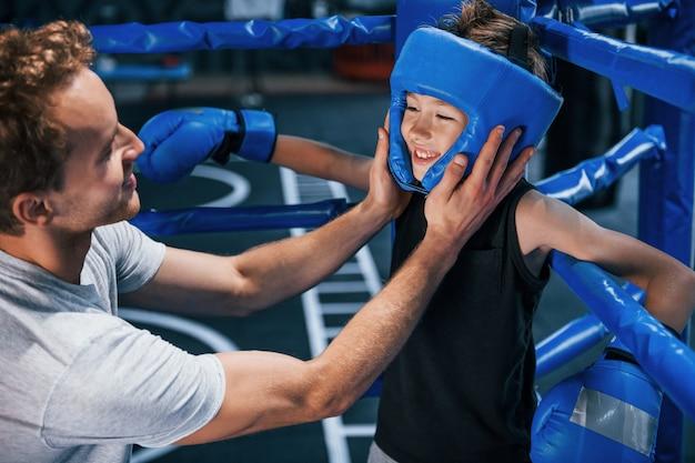 Молодой тренер по боксу помогает мальчику в защитной одежде на ринге между раундами.
