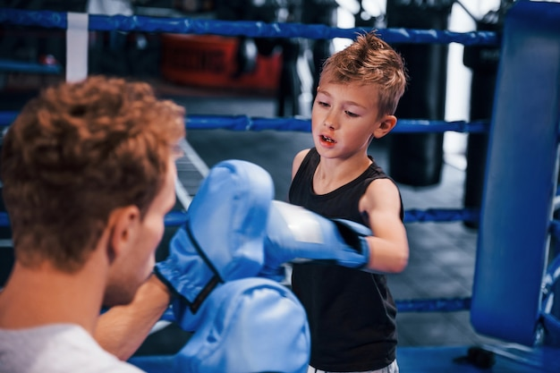 Young boxing coach is helping little boy in protective wear on the ring between the rounds.