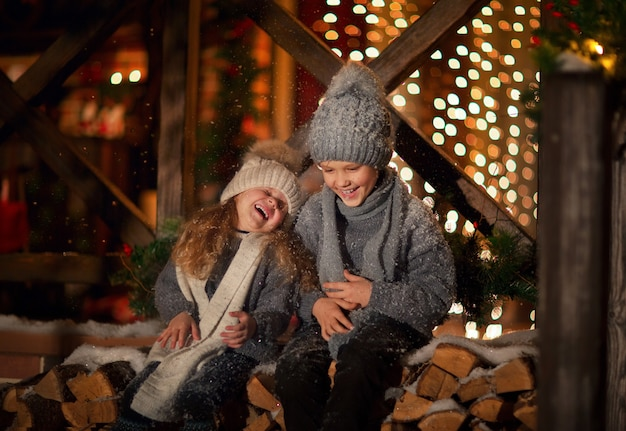 木の家の前に丸太の上に座っている灰色の冬の帽子、セーター、スカーフの少年と少女