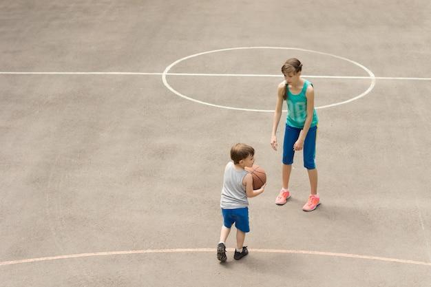 バスケットボールをする少年と少女