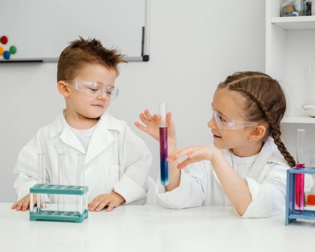 実験室で実験をしている少年と少女の科学者
