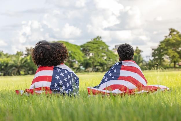 잔디 미국에 앉아 미국 국기와 어린 소년과 소녀 7 월 4 일을 축하