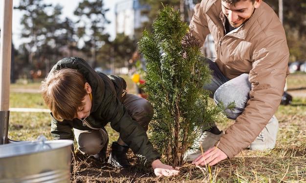 어린 소년과 그의 아버지는 야외에서 나무 심기