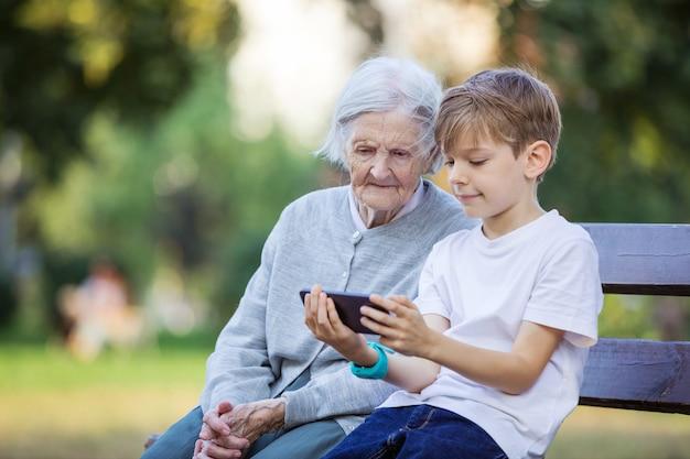 Молодой мальчик и его прабабушка смотрят видео на смартфоне. с помощью смартфона делать селфи.