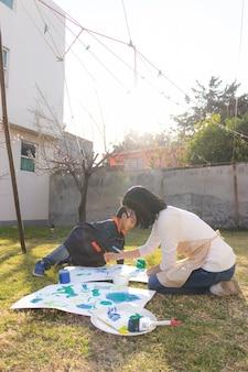 어린 소년과 젊은 여성이 작업복을 입고 흰색 표면에 브러시와 브러시로 그림을 그리고 배경에 옷이 놓여 있는 화창한 날 안뜰에서