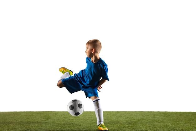 Молодой мальчик как футболист или футболист в спортивной одежде, делая финт или удар мячом по воротам на белом фоне студии. подходит играющего мальчика в действии, движении, движении в игре.