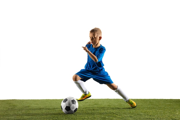 Молодой мальчик в футболе или футболисте в спортивной одежде, делая финт или ударяя мячом по воротам на белом.