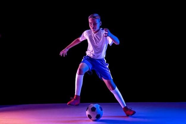 어두운 스튜디오 벽에 축구 또는 축구 선수로 어린 소년