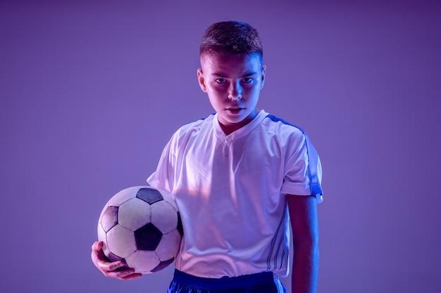 暗い壁にサッカーやサッカー選手としての少年