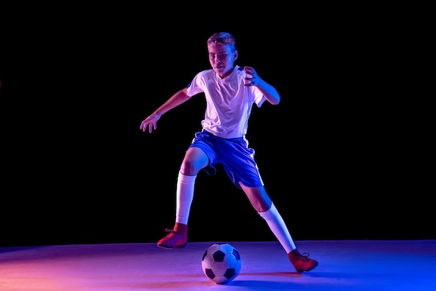Young boy as a soccer or football player on dark studio wall