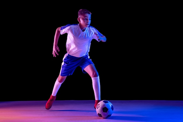 Young boy as a soccer or football player on dark studio